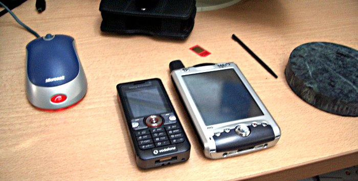 Sony Ericsson V630i next to an iPaq